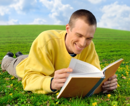 pleasure of reading: Man lying on a meadow and happily reading an amusing book, laughing