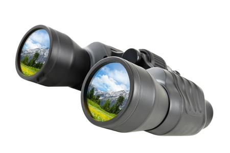 eyepiece: Studio shot of binoculars with the reflection of an inviting mountain landscape  Stock Photo