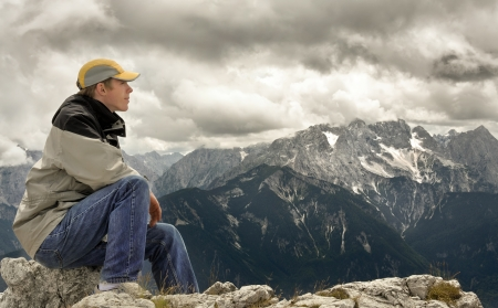 Young man sitting on a mountaintop and enjoying the majestic view photo