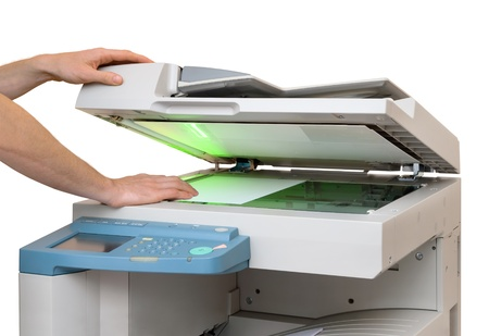 copier: Hands putting a sheet of paper into a copying device, isolated on white
