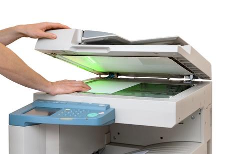 Ruce uvedení list papíru do kopírovacího zařízení, izolovaných na bílém Reklamní fotografie