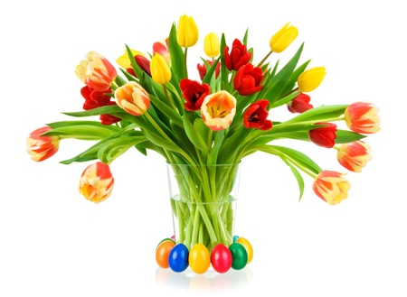 Gorgeous colorful bouquet of tulips in a glass vase, with easter eggs, isolated on white photo