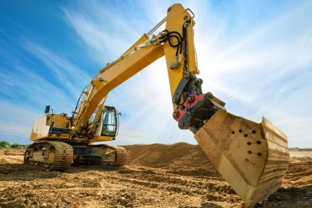 Excavadora grande en emplazamiento de la obra nueva, en el fondo del cielo azul y el sol