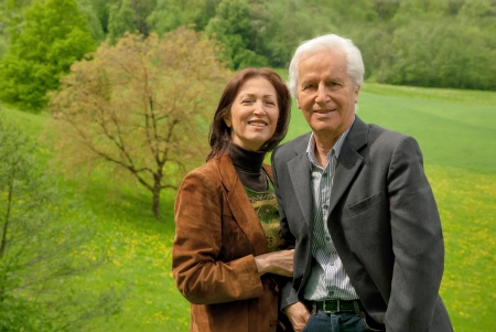 Happy senior couple standing on a meadow, enjoying themselves and smiling into the camera photo