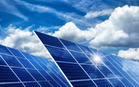 活気のある雲、太陽の反射と青空の下で 2 つの大規模な太陽電池パネル 写真素材