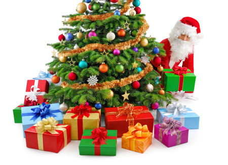 Santa Claus kneeing beside a gorgeous Christmas tree and putting the gift boxes in place Stock Photo
