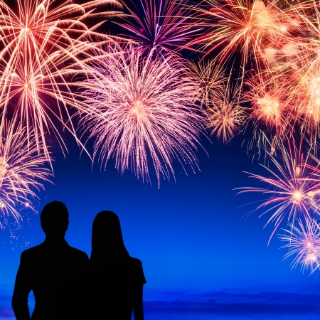 Spectacular fireworks display on deep blue sky with silhouettes of a young couple watching it Stock Photo