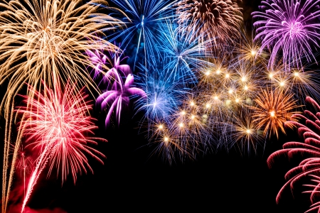 newyear night: Gorgeous multi-colored fireworks display on black background, with copyspace