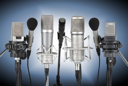 Studio-opname van zeven professionele microfoons in een rij op blauwe achtergrond met spotlight Stockfoto