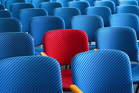 booked: Red seat as an eyecatcher in the middle of rows of empty blue seats, conceptual image