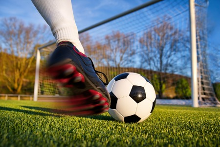 Football or soccer shot with a neutral design ball being kicked, with motion blur on the foot and natural background Stock Photo