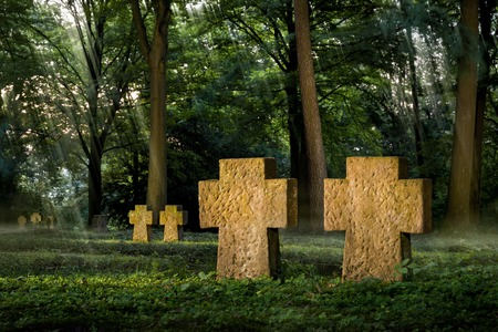 Cemetery with warmly illuminated cross shaped tombstones, while the background has a moody soft light atmosphere photo