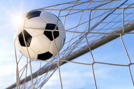 Football or soccer goal, with a neutral design ball flying into the net, blue sky and sun in the background photo