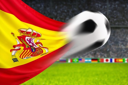 spiffy: Soccer ball in fast motion in front of the Spanish flag waving in a spiffy way in a football arena