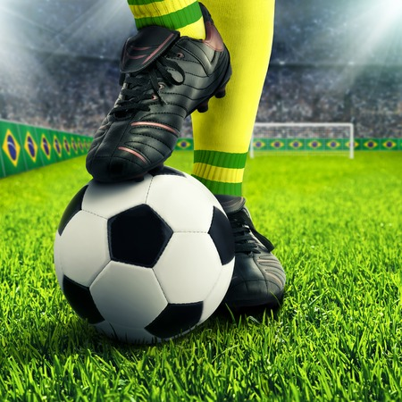 football socks: Brazilian soccer players feet in casual pose in a football arena, with the crowd in the background