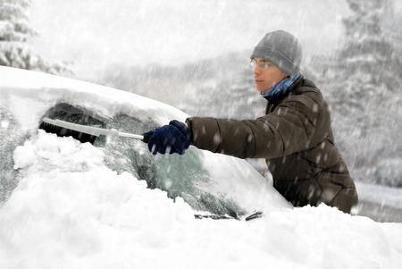 Junger Mann putzt den Schnee von seinem Auto an einem kalten Wintertag in Schneefall