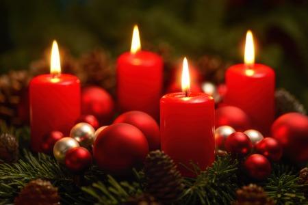 Low-Key-Studio-Aufnahme von einem schönen Adventskranz mit Kugeln und vier brennende rote Kerzen