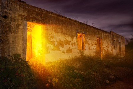 dodgy: Colorful night shot of an old abandoned house with mysterious warm light shining out from the entrance Stock Photo