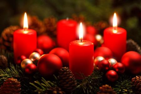 Low-key studio shot van een mooie komst krans met kerstballen en drie brandende rode kaarsen