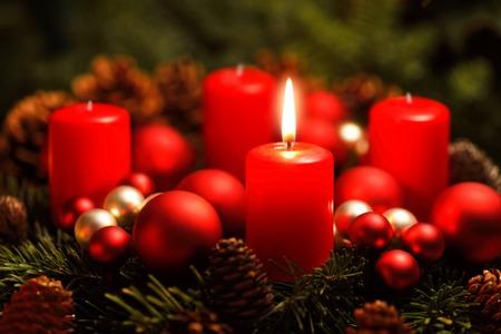 Low-Key-Studio-Aufnahme von einem schönen Adventskranz mit Kugeln und eine brennende rote Kerze
