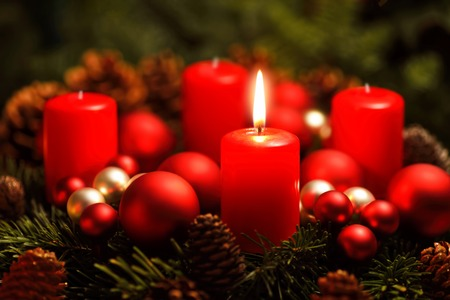1: Low-key studio shot of a nice advent wreath with baubles and one burning red candle