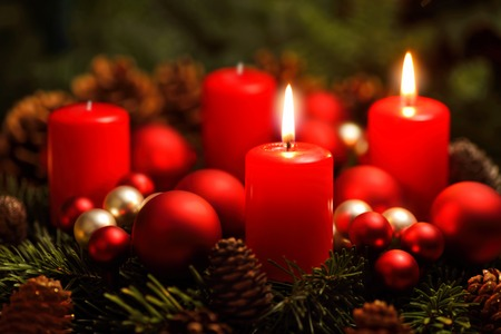 -Tiro oscuro del estudio de una bonita corona de adviento con adornos y dos velas ardientes rojos Foto de archivo - 33473658
