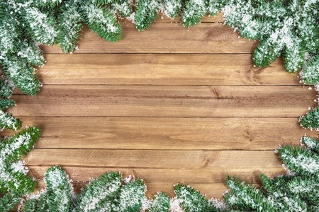 Wood planks background framed with snow covered fir twigs photo
