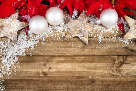 Christmas arrangement with poinsettia, wooden stars, white baubles and snowflakes bordering a rustic wood planks background