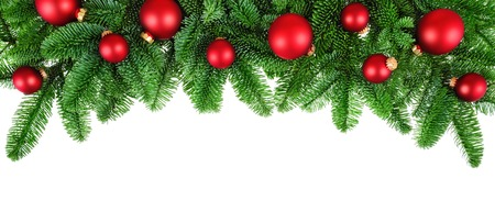 Studio isolated lush fir twigs with red baubles as a bow-shaped border on pure white background Standard-Bild