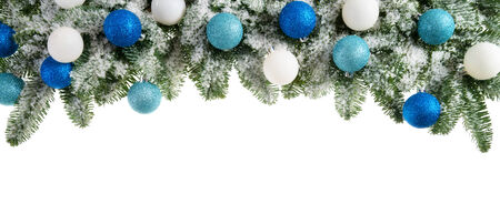 Studio isolated lush fir branches with snow and baubles in blue and white, as a bow-shaped border on pure white background photo
