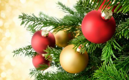 Kerstballen opknoping op een chique manier op weelderige groene takken van een verse dennenboom, met goud bokeh lichten op de achtergrond
