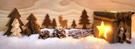 Beautiful Christmas arrangement with nice wooden ornaments and shining lantern, with wood board background, illustrating a conifer forest in snow, extra wide format Reklamní fotografie