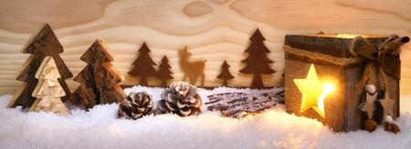Krásné Vánoce uspořádání s pěknými dřevěnými ornamenty a svítící lucerna, se dřevěná deska pozadí, znázorňující jehličnan les ve sněhu, extra široký formát Reklamní fotografie