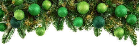 Studio isolated lush fir twigs with green baubles as a bow-shaped border on pure white background photo