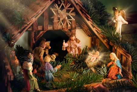 pesebre: Colorido escena de la natividad con el bebé Jesús, María, José, un ángel y otras figuras religiosas famosos de la biblia, mejorada con los rayos de luz de estado de ánimo devocional Foto de archivo