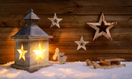 Cozy Christmas arrangement with beautiful wooden ornaments on snow in the warm candlelight of a nice lantern, low-key studio shot photo