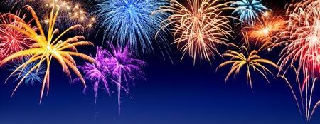 celebracion: Magníficos fuegos artificiales multicolores se muestran en azul oscuro cielo nocturno, con copyspace Foto de archivo