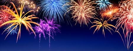 Gorgeous multi-colored fireworks display on dark blue night sky, with copyspace Banque d'images