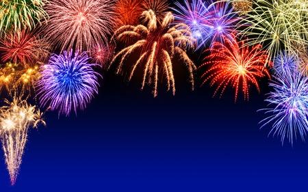 nouvel an: Magnifiques feux d'artifice multicolores affichent sur fond bleu ciel nocturne, avec copyspace