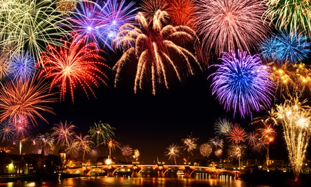 Cheerful fireworks display in the city, with lots of colorful bangs rising high into the night sky, with black copyspace