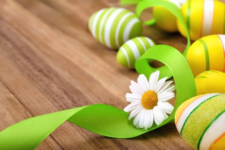 curved ribbon: Smart Easter decoration with happy bright spring colors of green, yellow and white on a wooden surface, with a daisy flower, curved ribbon and painted eggs