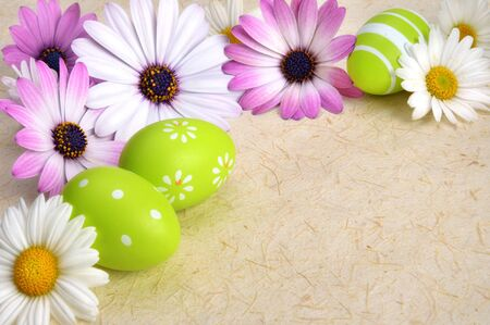 Bright-colored flowers and green Easter eggs as a border on rustic natural paper or parchment, with copysace photo