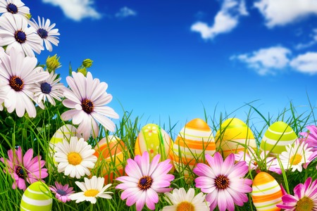 Spring flowers and happy colorful Easter eggs with a clear, deep blue sky in the background photo