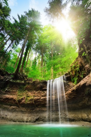 Fascinating wide-angle landscape shot of a paradise with waterfalls on multi-layered cliffs, fresh green forest, blue sky and the sun shining bright Stock Photo
