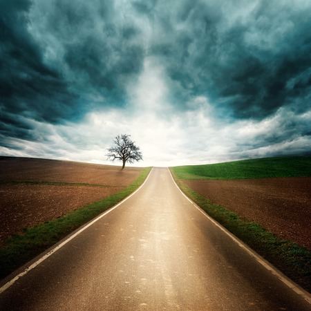 Lonely and moody road through empty fields with dramatic sky, dark clouds, interesting light and symmetrical composition Stock Photo