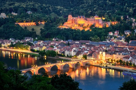 The city of Heidelberg, Germany, with its famous landmarks, the illuminated historic castle and the Old Bridge on Neckar river, shot at dusk