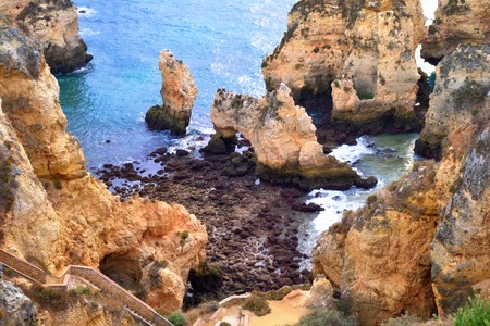 Lagos: Scenic landscape showing a beautiful coast with steep large cliffs and the blue ocean water, shot in Lagos, Algarve, Portugal