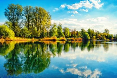 Paisagem tranquila em um lago, com o céu vibrante, nuvens brancas e as árvores refletidas simetricamente na água azul limpa