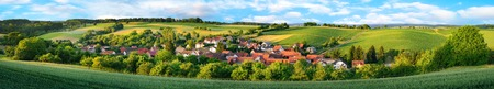 vicinity: Super wide panorama of a small German village surrounded by green landscaped hills Stock Photo