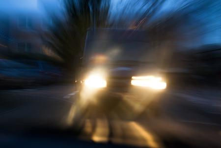 Krytý vůz blíží v hrozivým způsobem v soumraku, s úmyslným chvění fotoaparátu pro koncepci rizik autonehodu